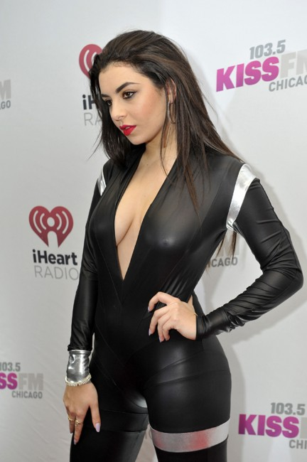 Charli XCX boobs show in black dress at an event